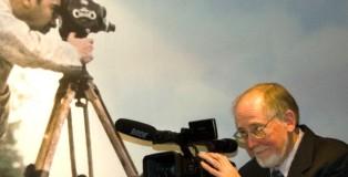 """Sam Bryan na tle zdjęcia ojca na wstawie """"Amerykanin w Warszawie w DSH. Fot. Jerzy Sieradzki"""